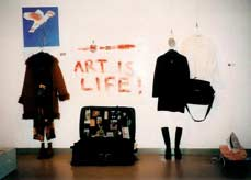 photo of installation in gallery including clothing and suitcase.